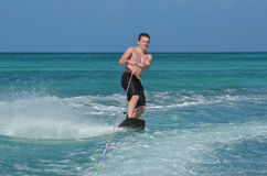 Aruba Young Man Riding a Wakeboard on a Warm Day. Beautiful Aruba with a young man riding a wakeboard on a warm day Stock Image