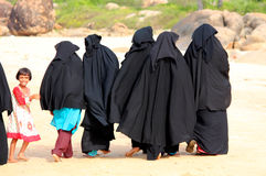 ARUGAM BAY, AUGUST 13: A group of Muslim women walking down the beach with a little girl Royalty Free Stock Photography