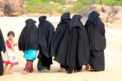 ARUGAM-BUCHT, AM 13. AUGUST: Eine Gruppe moslemische Frauen, die hinunter den Strand mit einem kleinen Mädchen gehen Lizenzfreie Stockfotografie