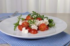 Arugula σαλάτας με τις ντομάτες και τη μοτσαρέλα κερασιών Στοκ Εικόνα