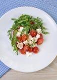 Arugula σαλάτας με τις ντομάτες και τη μοτσαρέλα κερασιών Στοκ Φωτογραφία