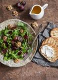 Arugula, σταφύλια, σάντουιτς σαλάτας και τυριών στον ξύλινο πίνακα Στοκ Εικόνες