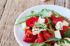Arugula φέτας και σαλάτα ντοματών στο άσπρο πιάτο Στοκ Εικόνες