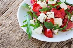 Arugula φέτας και σαλάτα ντοματών στο άσπρο πιάτο Στοκ Φωτογραφίες