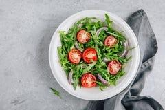 Arugula de salade verte avec les tomates et l'oignon rouge dans la cuvette Photo libre de droits