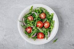 Arugula de salade verte avec les tomates et l'oignon rouge dans la cuvette Image libre de droits