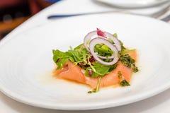 Arugula et oignon sur les saumons fumés Photographie stock libre de droits