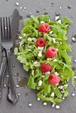 Arugula with feta and raspberries. Arugula with feta and fresh raspberries   on a slate board Royalty Free Stock Image
