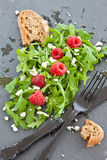 Arugula with feta and raspberries. Arugula with feta and fresh raspberries   on a slate board Royalty Free Stock Photography