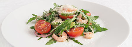 Arugula leafs, cherry tomatoes, prawns, avocado, and red onion  salad sprinkled with grated cheese Stock Image
