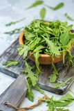 Arugula leaves in a wooden bowl. Bowl of fresh arugula on an old serving board, selective focus royalty free stock image