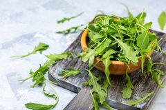 Arugula leaves in a wooden bowl. Bowl of fresh arugula on an old serving board, selective focus royalty free stock photo