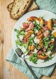 Arugula, prosciutto, μοτσαρέλα και ψημένη στη σχάρα σαλάτα ροδάκινων στο άσπρο πιάτο Στοκ Φωτογραφία