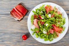 Arugula, prosciutto, σαλάτα μοτσαρελών σε ένα άσπρο πιάτο Στοκ Φωτογραφίες