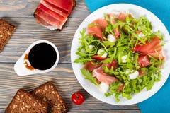 Arugula, prosciutto, σαλάτα μοτσαρελών σε ένα άσπρο πιάτο Στοκ εικόνες με δικαίωμα ελεύθερης χρήσης