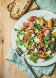 Arugula, prosciutto, mozzarella i piec na grillu brzoskwini sałatka w bielu talerzu, Fotografia Stock