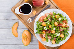 Arugula, prosciutto, mozzarella and melon  salad , top view Royalty Free Stock Photo
