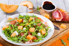 Arugula, prosciutto, mozzarella and melon salad , top view. Arugula, prosciutto, mozzarella salad and melon on a white dish on a wooden table, top view stock image