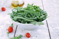 Arugula salad. On wooden table Stock Photos