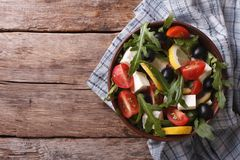 Arugula salad with cheese and tomatoes, horizontal top view Stock Photo