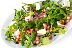 Arugula salad with feta cheese and pomegranate on a white plate Royalty Free Stock Images