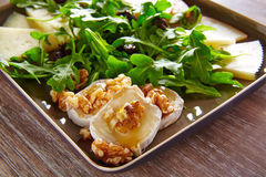 Arugula salad with goat cheese honey and nuts. Arugula mediterranean salad with goat cheese honey and nuts stock image