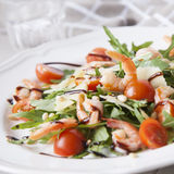 Arugula salad1. Italian salad with shrimps, arugula, tomatos, parmesan cheese, pine nut, olive oil and vinegar dressing on white plate. selective focus stock photo