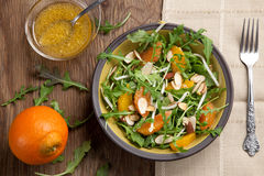 Arugula Salad with Mandarin Vinaigrette. Closeup of a plate of arugula salad with mandarins, oranges, beans sprouts, and sliced almonds served with mandarin royalty free stock photos