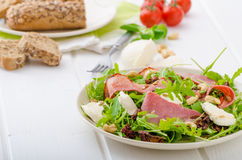 Arugula salad with meat and mozzarella. Arugula salad with smoked rump, sundried tomatoes, cashew nuts and mozzarella, wholemeal baguette royalty free stock image