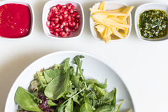 Arugula salad with pomegranate seeds and sauce, pesto sauce and. Freshly cut avocado in bowls on white background royalty free stock photography