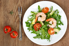 Arugula salad with prawn. Arugula salad with prawn on plate on a wooden table royalty free stock image