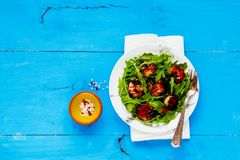Arugula salad with shrimp. Flat lay of arugula salad with grilled prawn shrimp on blue painted wooden copy space background. Healthy balanced eating. Top view Stock Photography