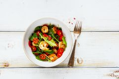 Arugula salad with shrimp. Flat-lay of fresh arugula salad bowl with prawn shrimp and tomatoes on white wooden copy space background. Healthy food concept. Top Royalty Free Stock Image