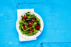 Arugula salad with shrimp. Fresh arugula salad with grilled prawn shrimp on blue painted wooden copy space background. Healthy balanced eating. Flat lay, top Stock Photography