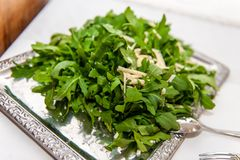 Arugula salad on silver platter. Arugula salad with parmesan cheese splitters on solid and beautiful silver platter on table with white cloth stock image