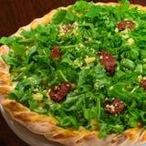 Arugula and sundried tomato pizza. A hole arrugula and sundried tomato pizza on a wood table Stock Photography