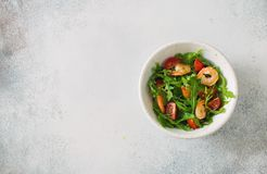 Arugula, tomatoes and shrimps salad on blue stone background. Top view. Copy space Royalty Free Stock Photography