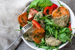 Arugula, vegan lentil fried cutlets, baked sweet potato Stock Image