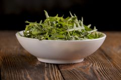 Arugula in a white plate on a wooden table Stock Photo