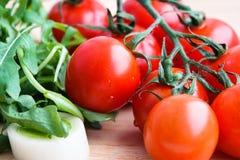 Arugula y puerro del tomate en la tabla de madera imagen de archivo