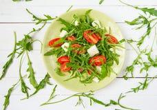 Arugulasallad med körsbärsröda tomater Arkivfoto