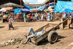 Africa market. Man lying on a wooden cart sleeps. Market Arusha, Tanzania, Africa Royalty Free Stock Image