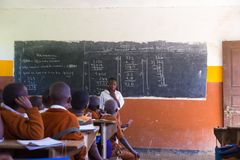 Children in uniforms in primary school classroom listetning to teacher in rural area near Arusha, Tanzania, Africa.