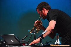 Arve Henriksen playing piccolo trumpet while moving MIDI controller, Elektrarna Piestany, Slovakia, 25th of august 2017. Picture taken during his performance Royalty Free Stock Image