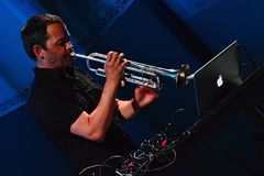 Arve Henriksen plays trumpet in front of his ibook and MIDI controllers, elektrarna Piestany, 25th of August 2017. Arve Henriksen plays trumpet in front of his Royalty Free Stock Photography