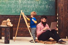 Arytmetyki lekcja przy szkołą Żartuje writing na chalkboard podczas gdy skoncentrowany nauczyciel pracuje na laptopie Bocznego wi obraz stock
