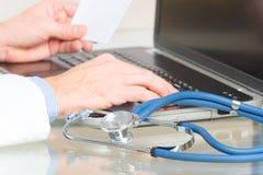 Arzt, der auf Laptop schreibt Lizenzfreies Stockbild