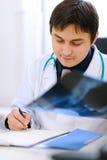 Arzt, der die Patienten Röntgen analysiert Lizenzfreie Stockfotografie