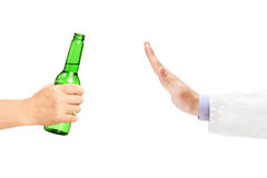 Arzt, der eine Flasche Bier ablehnt Stockbild