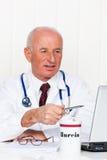Arzt in der Praxis mit Stethoskop und Laptop. Stockfotos